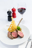 Dish of lamb cutlets paired and glass of wine at C'est Bon Restaurant, Cairns