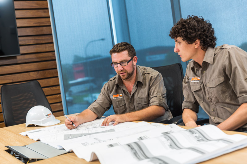 Two fuel service workers checking building plans at an office desk, Cairns