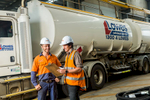 Two workers looking at maintenance checklist with a fuel tanker behind, Cairns