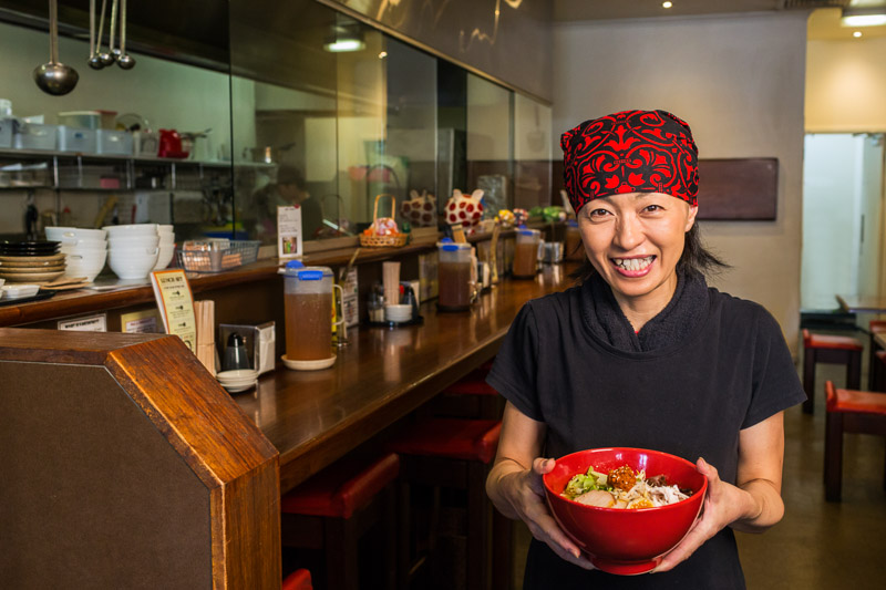 Image of Japanese noodle business owner holding a bowl or ramen noodles