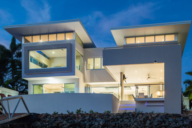 Exterior of waterfront home illuminated at twilight, Cairns