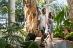 Asian couple walking with luggage at The Reef House, Palm Cove