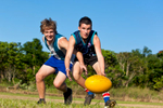 Two male students jostling for the AFL ball on the sports field, Cairns