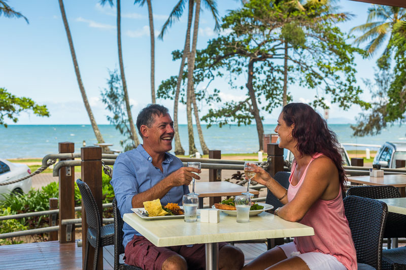 Mature couple enjoying lunch at a beachside cafe