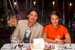 Portrait of My Kitchen Rules judges, Colin Fassnidge and Rachel Khoo sitting at dining table