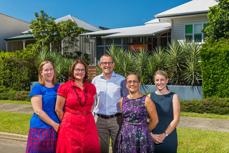 Group photo of law firm employees with business building in background, Cairns