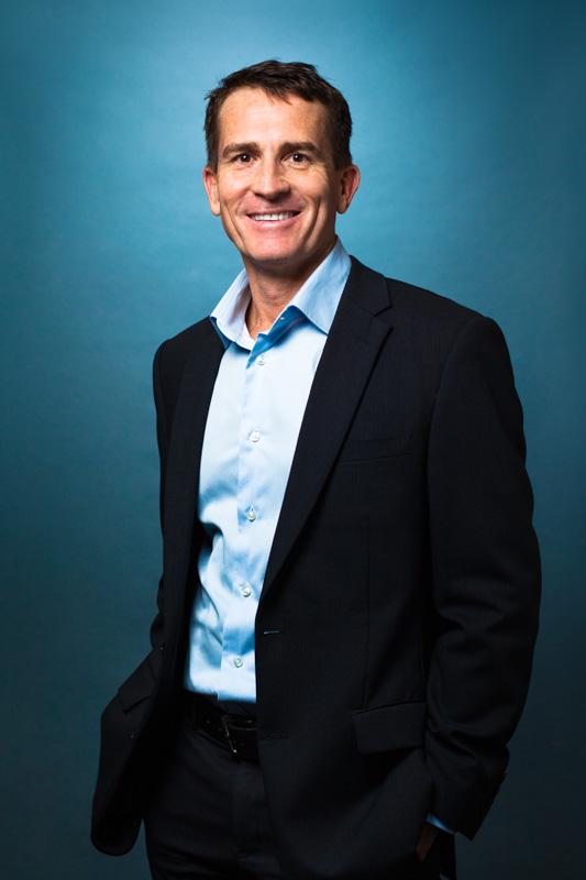 Portrait of Cairns financial services executive shot against blue background