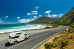 A campervan driving along a beautiful coastal road with blue skies