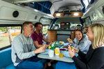 A group of young travellers eating dinner inside a campervan