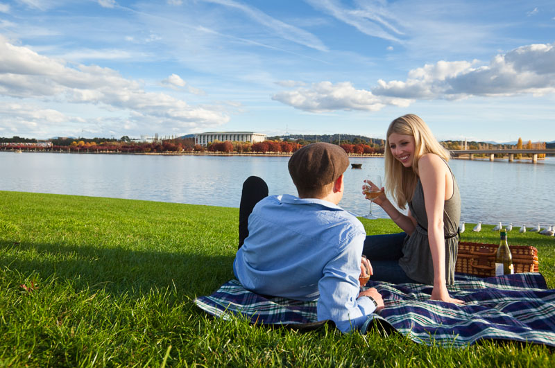A youple relaxing on a picnic blanket on the edge of a city lake
