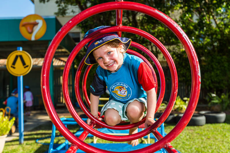 A young child playing on rings in an early learning centre playground