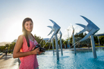 Young woman with camera standing in front of fish sculpture at Cairns Esplanade Lagoon
