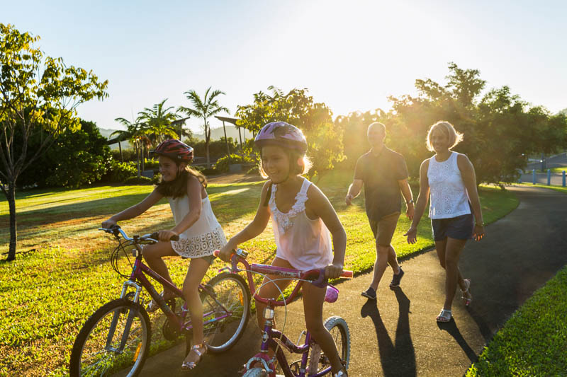 A young family with two kids on bikes walking through a park