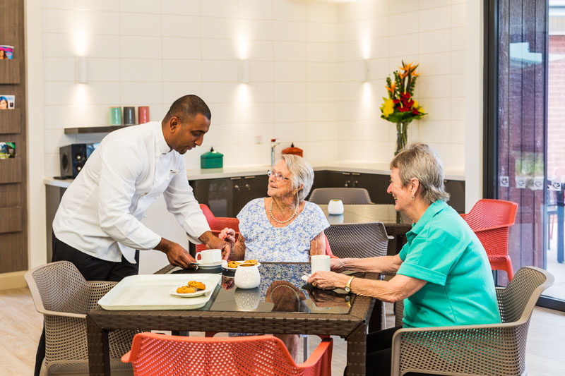 A kitchen staff member serving residents and family at an aged care centre