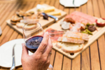 Hand holding wine glass with food platter in backgroudn at Brown Brothers in Milawa, Victoria