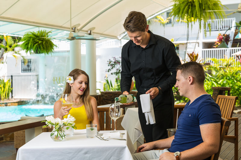 Couple being served wine by waiter, poolside at The Reef House Palm Cove, Cairns