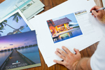 Designer looking at tourist publication mockups at Koolivoo offices in Cairns