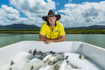 Portrait of manager and farmed barramundi on ice at Sealord King Reef Barramundi Farm, near Cairns