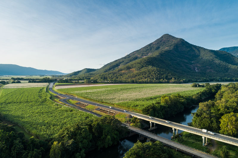 Aerial view of highway bridge over Mulgrave River, with Walsh's Pyramid beyond, Cairns