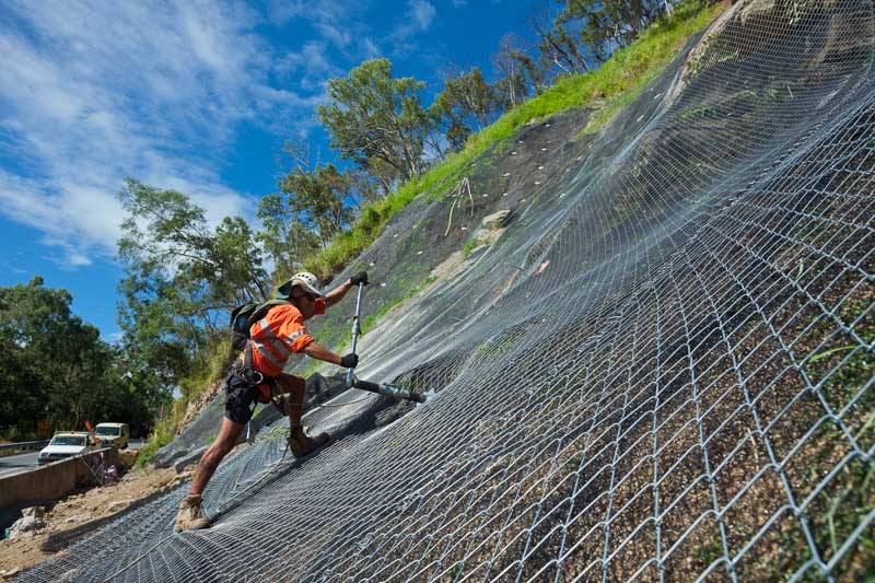 Worker securing mesh on a slope stabilization project, Cairns