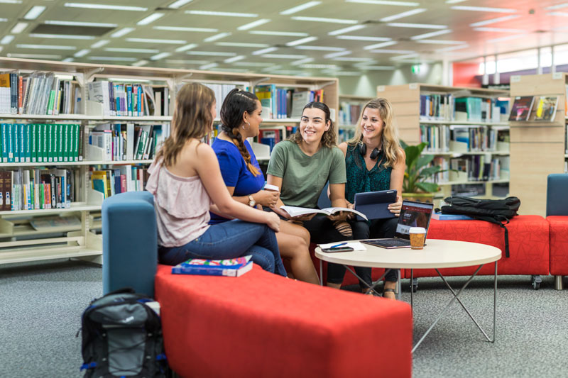 A group of tertiary education students talking together in the library