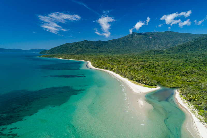 Aerial view of clear waters, white sand beach and rainforest along the Daintree coast