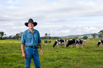 A dairy farmer in paddock with cows in background, Malanda