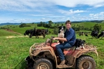 Portrait of a dairy farmer and his work dogs sitting on a quad bike at a farm