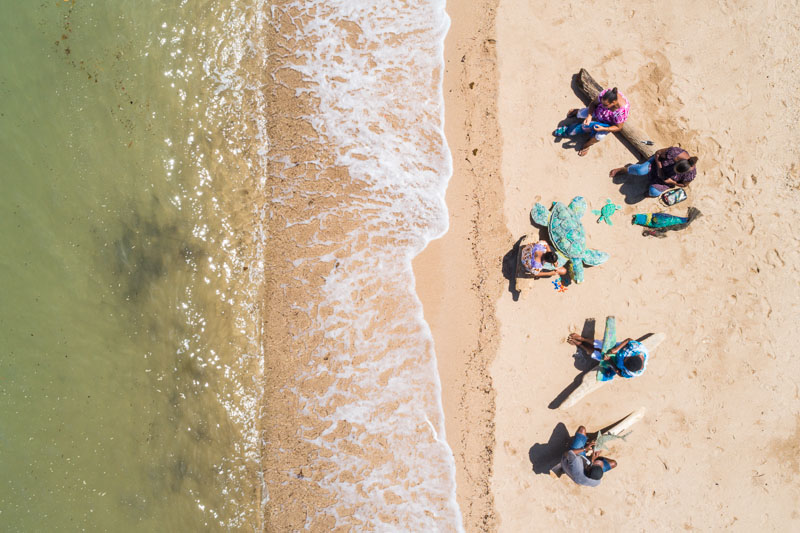 Aerial view of artists weaving ghost net art on the beach, Erub Island