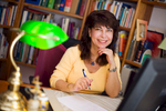 Portrait of female author smiling and sitting at home office desk