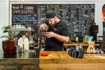 A cafe barista at counter pouring crema into an espresso coffee