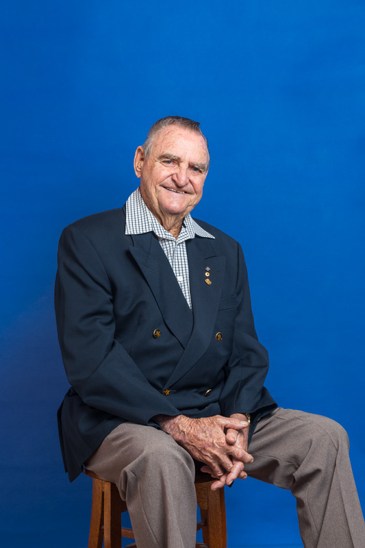 Portrait of war veteran seated in front of blue background