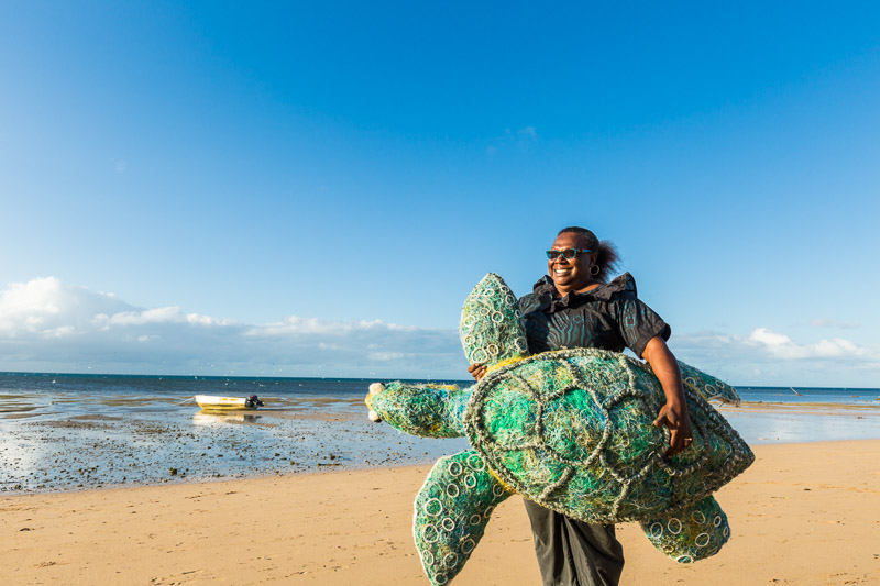 Erub Island woman holding a turtle artwork made from ghost nets