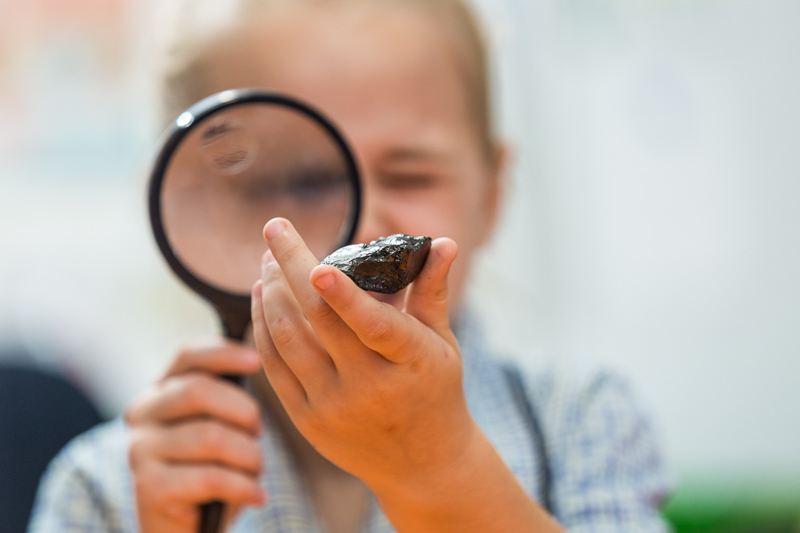A young school student peering through a magnifying glass to view rock
