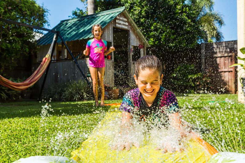 Young girl having fun on backyard waterslide with sister watching on