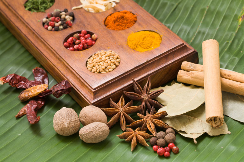 Mixed spices including nutmeg, star anise and cinnamon on a banana leaf