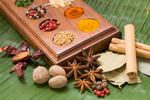 Mixed spices including nutmeg, star anise and cinnamon on a banana leaf