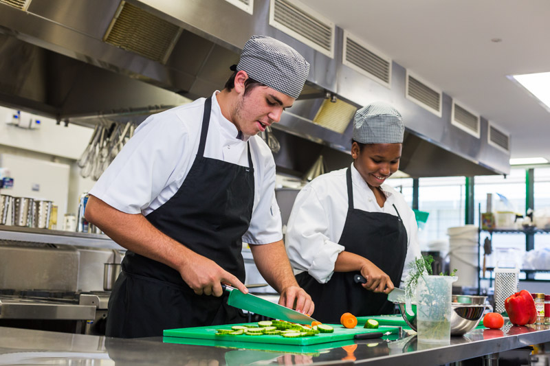High school students practising food preparation skills in a commercial kitchen