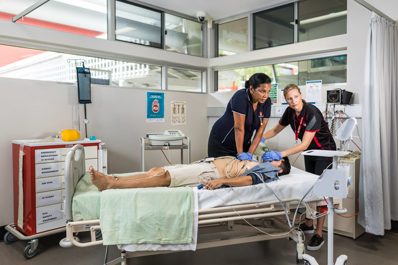 A nursing student practicing CPR with her teacher watching on, Cairns