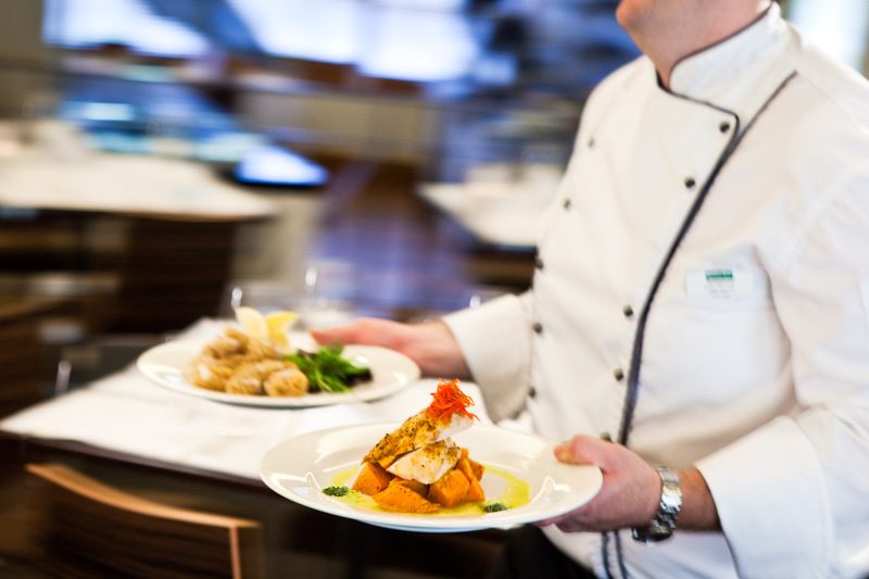 Chef carrying plates of food through restaurant at Holiday Inn Cairns