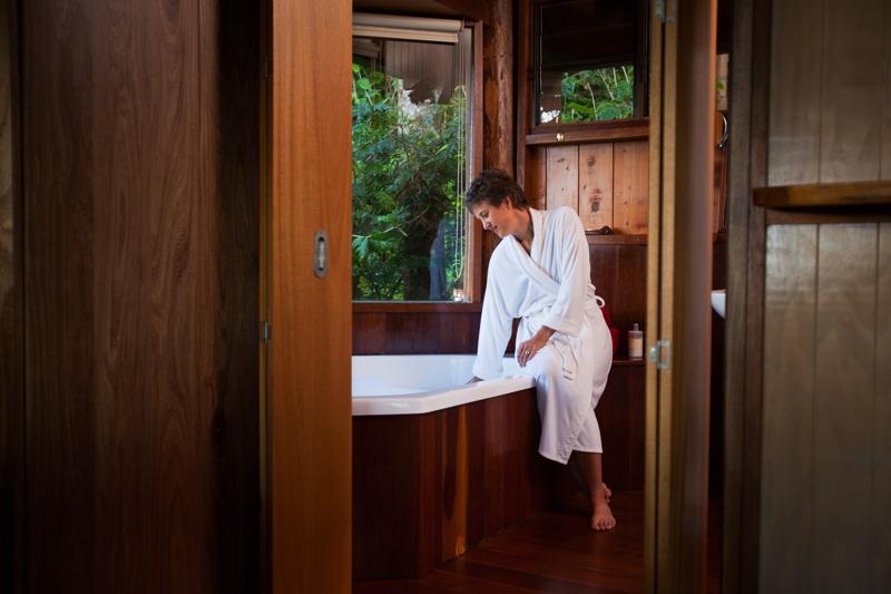 Woman in bathrobe preparing a bath at Rose Gums Wilderness Retreat
