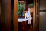 Woman in bathrobe preparing a bath at Rose Gums Wilderness Retreat