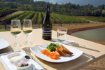 A restaurant dish and wines overlooking vineyards