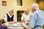 Elderly residents at a retirement village playing a game of cards