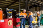 Maintenance workers in high visibilty clothing talking in workshop, Cairns