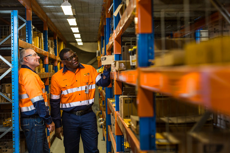 Two workers checking stores shelves at an earthmoving equipment business, Cairns