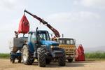 Farmers unloading fertilizer using a crane at a cane farm, Atherton Tablelands