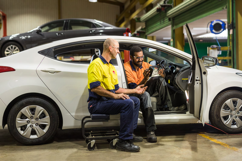 An automotive supervisor instructing a student on a test vehicle, Cairns