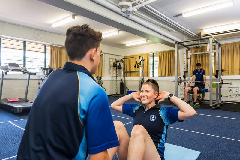 Male and female students doing situp exercises in the school gym