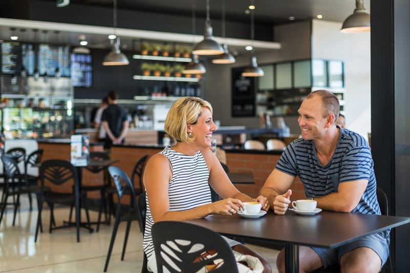 A couple chatting and relaxing with a coffee in a cafe